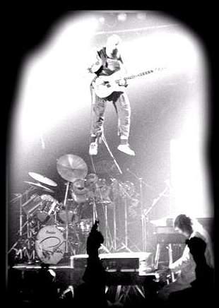 John McCoy flying over Mick Underwood's drum rise